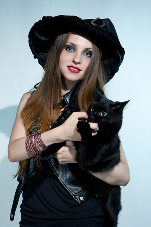 belonging to the caucasoid race: Beautiful witch with black cat. Halloween. Stock Photo