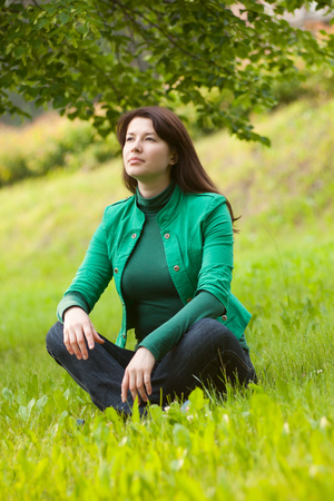 reverie: Happy young woman sitting on grass and falling into a reverie
