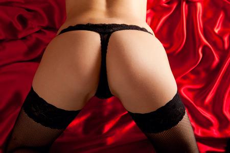 Arsch in sexy Dessous auf roter Seide Standard-Bild