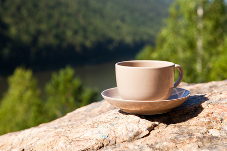 Cup on big stone over nature background. With place for text. Stock Photo