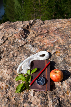 Notebook, compass, apple, rope on old stone background photo