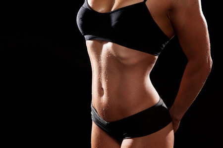 perspiration: Sporty muscular woman on black background.