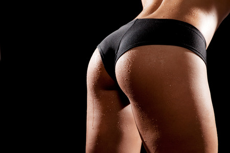 Young tanned woman with beautiful sporty buttocks wearing black sexy sporty style shorts. Water drops on wet skin photo