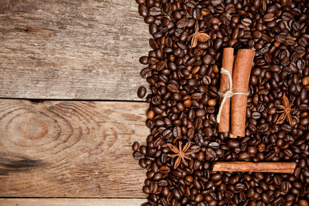 Coffee beans, cinnamon, star anise on old wooden table. Top view. photo