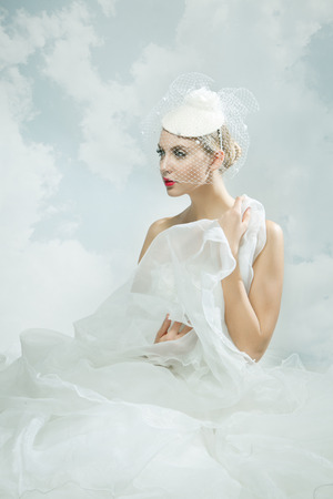 Beautiful bride over the sky background. Vintage style. photo