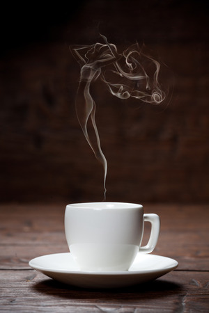 Cup of coffee with woman-shaped smoke on dark wooden background Archivio Fotografico