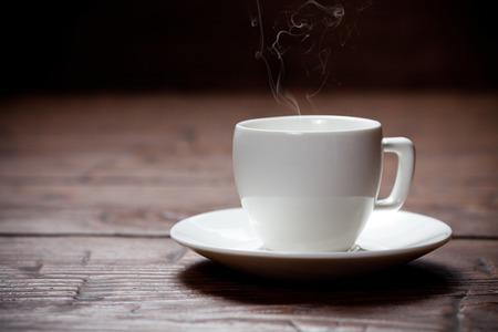 filiżanka kawy: Filiżanka kawy i spodek na starym drewnianym stole. Ciemne tło. Zdjęcie Seryjne