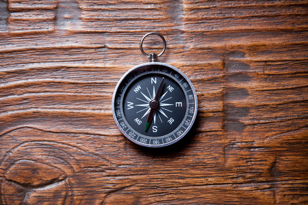 compass on wooden background with space for text