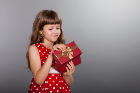 christmas gift: Little girl in vintage spotted red dress holding her present