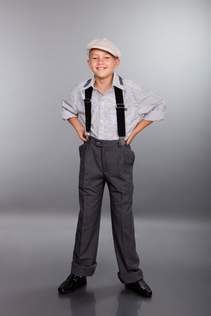 suspender: Old fashioned boy looking to the camera on gray background Stock Photo