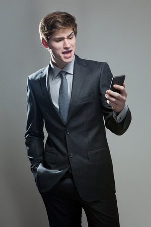 disenchantment: Young businessman using a mobile phone, on gray background