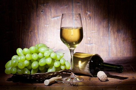 Wine bottles, bunch of grapes and glass of white wine on old wooden background