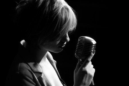レトロなマイクを使って歌う女性。 写真素材