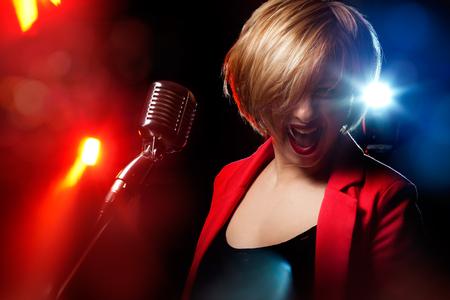 Zingende vrouw met retro microfoon.