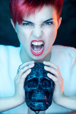Portrait of beautiful woman in white jacket with fake black skull head in her hands Stock Photo