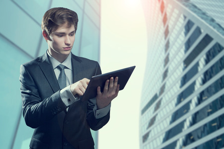 Portrait of young businessman with touch screen computer, in an urban setting