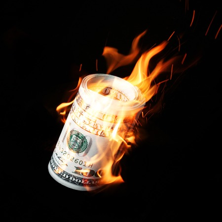 arsonist: Burning one hundred dollar bills rolled black background