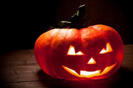 tallado en madera: Scary Calabaza de Halloween en un fondo de madera vieja. Scary brillante caras truco o Foto de archivo