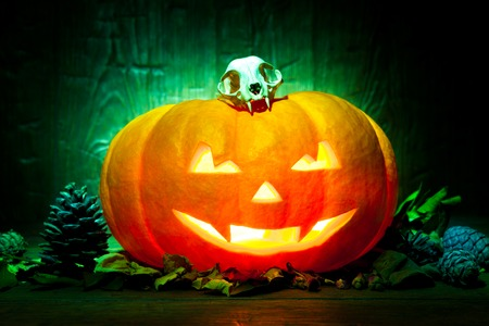 Scary Halloween pumpkin on a old green wooden background. Scary glowing faces trick or treat Stock Photo