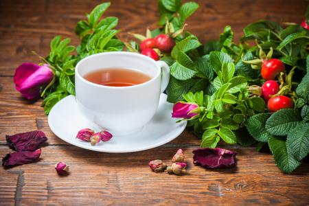 Tè sano con una rosa canina sul vecchio tavolo di legno