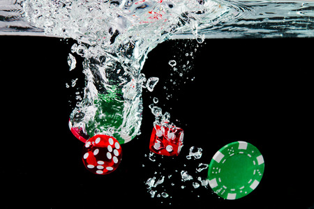 Red dice and chips in the water on black background. Visible splash and air bubbles.