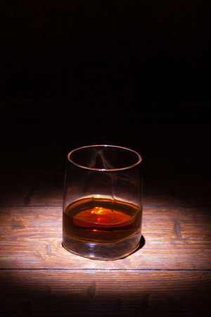 Glass of whiskey on old wooden table with place for text