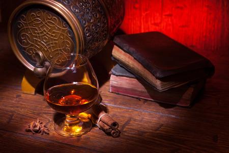 Glazen whisky, boeken, kaneel, steranijsplant en klein voordeelvat op oude houten lijst met rode achtergrond. Vintage stilllife.