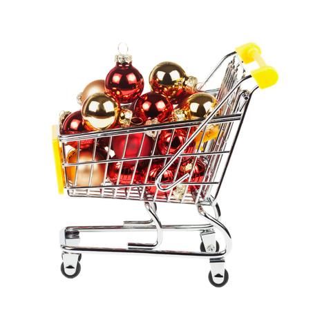 Bolas de Navidad en el carro de compras aislado en el fondo blanco. Concepto de la venta del Año Nuevo.