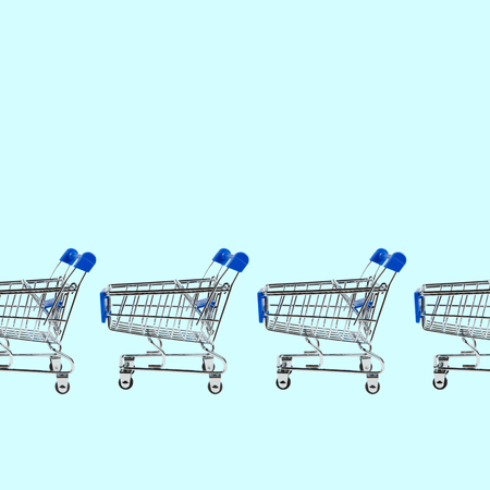 Shopping cart isolated on blue background with place for text. Sale concept.