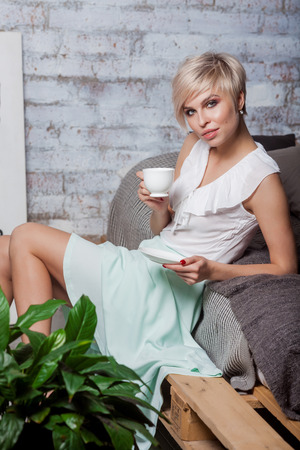 Beautiful woman lying on bed. Coffeebreak in loft interior. Standard-Bild