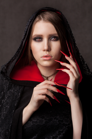 Vintage style portrait of young beautiful vampire woman with gothic Halloween makeup Фото со стока