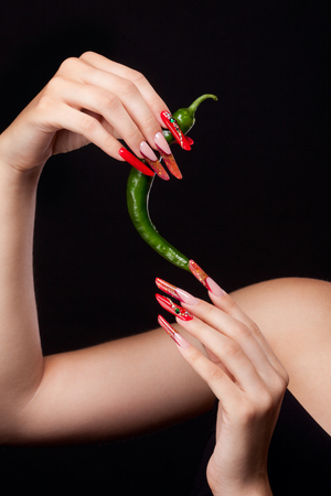 Trendy manicure and red lips with green chili pepper.