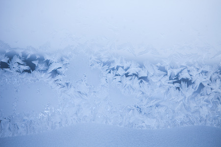 Abstract blue frosty pattern on glass. Winter background. Stock Photo