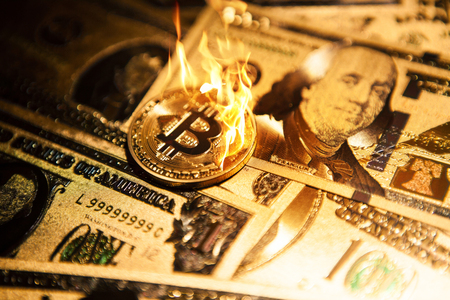 Burning golden bitcoin cryptocurrency on golden US dollars. Stock Photo