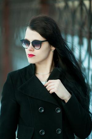 Junge Frau, die im schwarzen Mantel und im schwarzen Hut aufwirft.