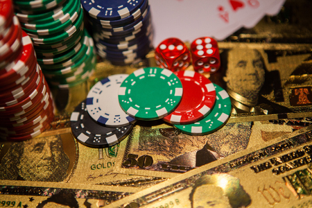 Casino red dices and casino poker chips on golden US Dollar bills