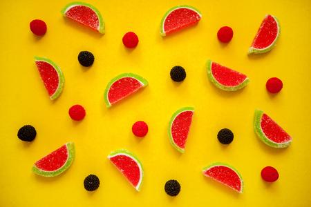 Fruit jelly segments in the form of watermelon on yellow 版權商用圖片