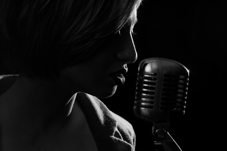 Silhouette of singing woman with retro microphone
