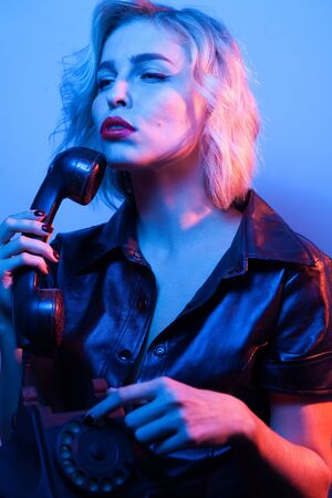 Attractive woman dressed in fashion apparel with phone in neon night lights.