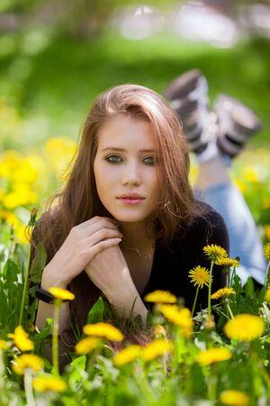 Image of pretty woman lying down on dandelions field.