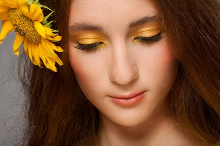 Woman with stylish colorful makeup and sunflowers Stock Photo