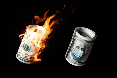COVID-19 coronavirus in USA. Roll of hundred dollars money bill with face mask and in fire. Standard-Bild