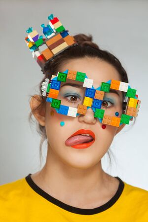 Young beautiful woman playing with building plastic blocks toy.