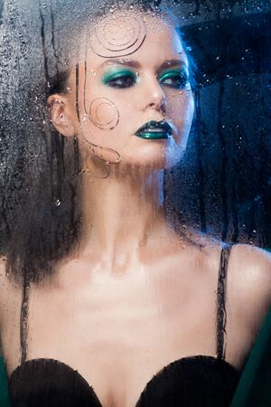 Beautiful model girl stands behind a glass with raindrops.