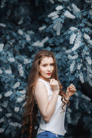 Portrait of woman on a background of blooming bird cherry. Stok Fotoğraf