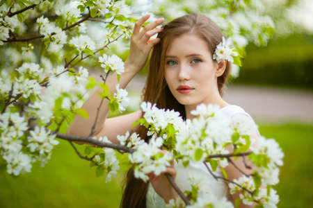Portrait of woman on a background of blooming apple tree.