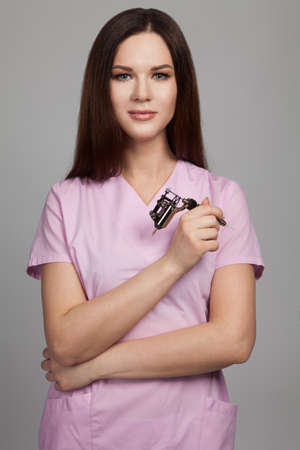 the permanent makeup tattoo artist stands against a gray background in a uniform pink Stok Fotoğraf