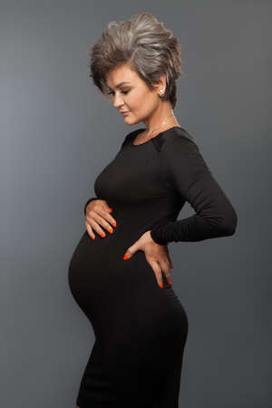 Portrait of loving pregnant woman looking at belly while posing