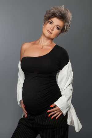 Portrait of loving pregnant woman looking at camera while posing