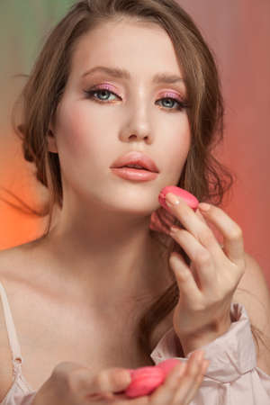 Beauty fashion model girl with delicate makeup and manicure taking pink macaroons
